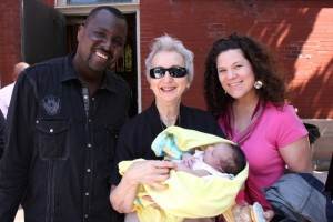 Sr. Mary Margaret holding Marguerite Marie for the first time, next to parents François and Melissa