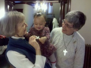 Baby Marguerite Marie embraces the Sister's cross on Vow Renewal Day