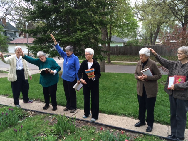 "Processing out singing ""Canticle of the Sun"" and the Garden Blessing: S. Katherine tossing earth, S. Suzanne reading the prayer"